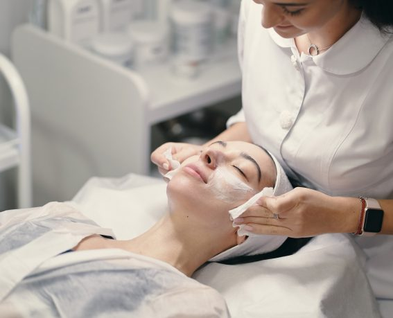 Woman lying during cosmetic procedure while skillful female cosmetologist making facial treatment